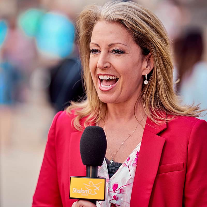 Kendra as Shalom TV News Anchor