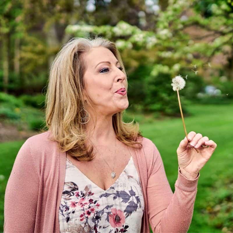 Kendra Von Esh blowing a dandelion